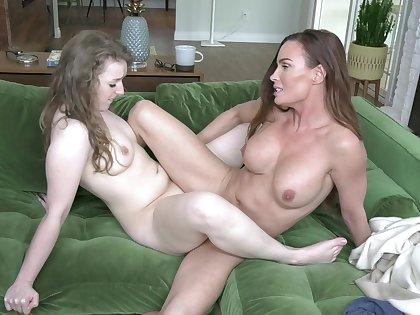 Aroused women share passionate scissoring on the sofa