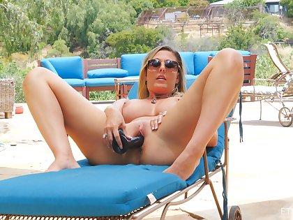 Awesome blonde MILF Jayna masturbates adjacent to an upscale pool